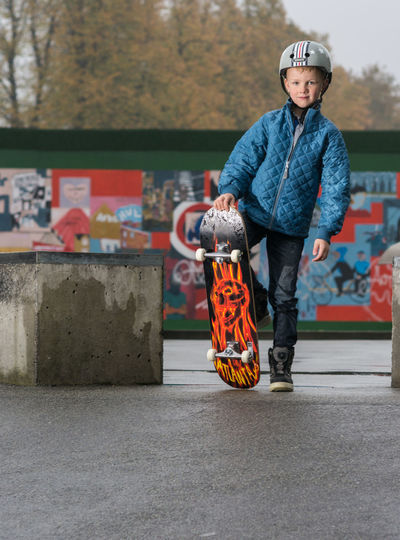 Portrait of boy with skateboard at park