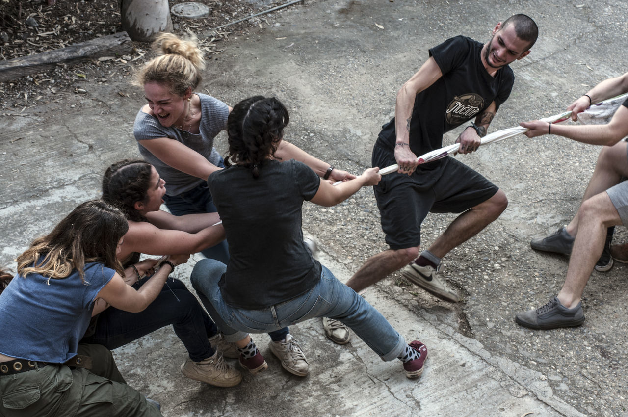 High angle view of friends playing tug-of-war on street
