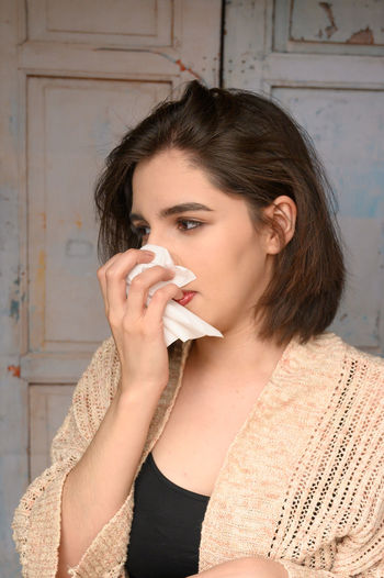 Close-up of woman covering nose with tissue