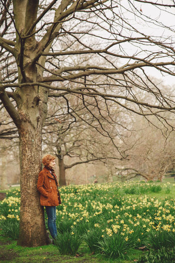 Woman standing by tree at park