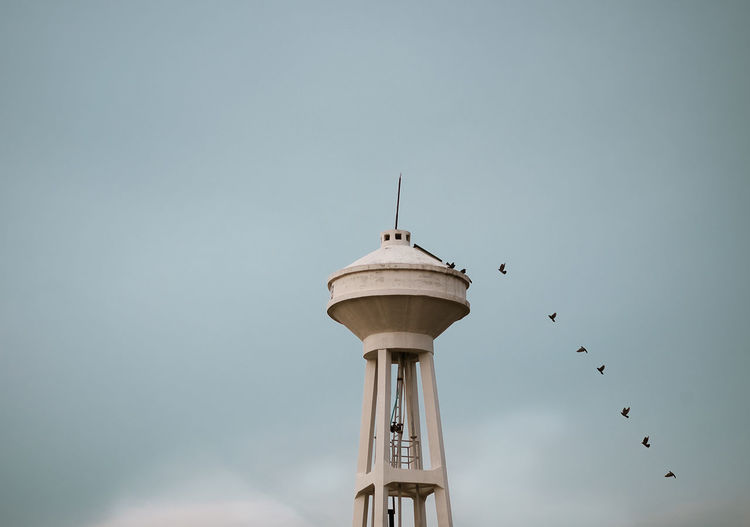 Low angle view of birds flying by tower against sky
