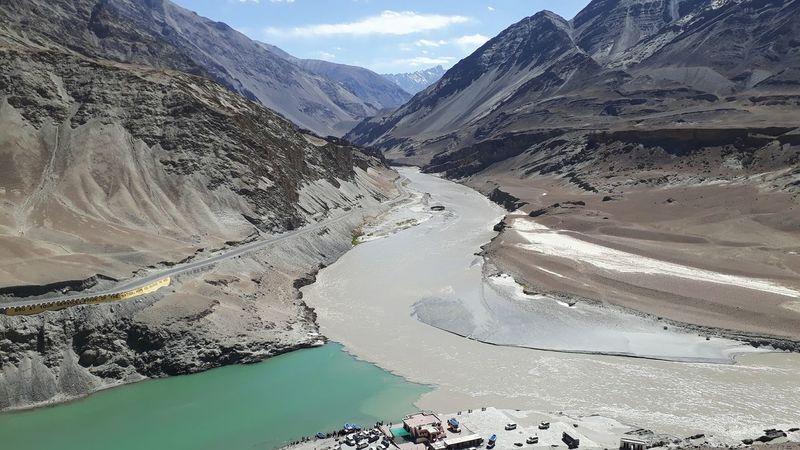 The Sindhu-Zanskar Confluence Sindhu Zanskar River Riverconfluence Indus River Muddy Waters Aquamarine Water Mountain River Sky Landscape Mountain Range Rugged Rocky Mountains Arid Landscape