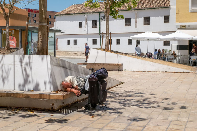 Tired tourist sleeping on a bench in Enrique Garcia Herrera square, Malaga city, Spain Garcia Malaga Square Tired Tourists Architecture Building Building Exterior Built Structure City Day Enrique Footpath Full Length Herrera Hopelessness Incidental People Lifestyles Men Nature Outdoors People Plazza Real People Rear View Sidewalk Sleaping Social Issues Street The Photojournalist - 2018 EyeEm Awards The Street Photographer - 2018 EyeEm Awards Summer In The City
