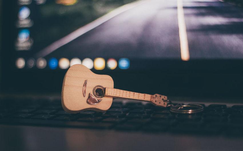Close-up of figurine guitar on laptop