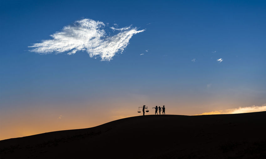 Low angle view of silhouette people on landscape against sky during sunset
