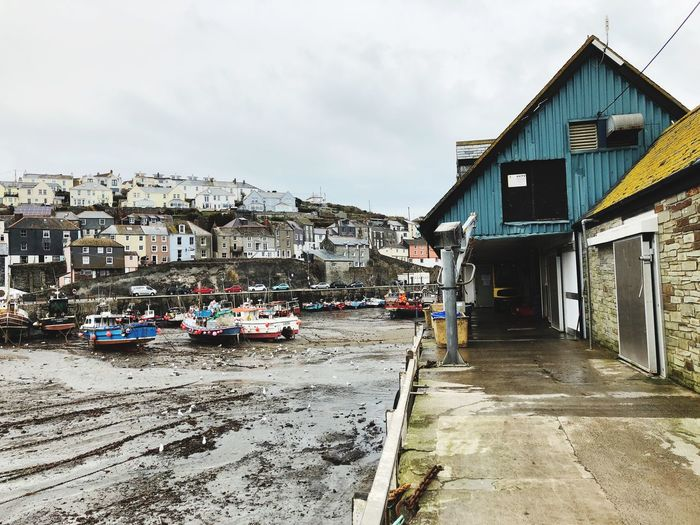 Fishing village in Cornwall at low tide Cornish Coast English Coast Seagulls Ebb Tide Sand Low Tide Harbour Cornish Village Architecture Built Structure Text Building Exterior Sky Day Outdoors No People