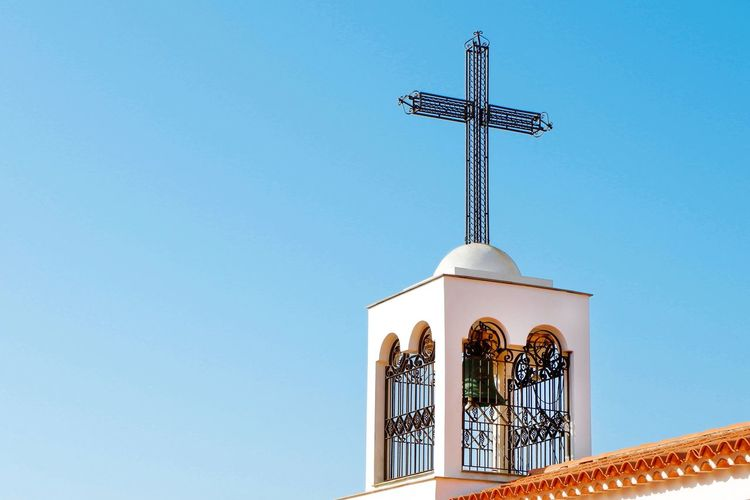 Low angle view of cross and building against clear blue sky