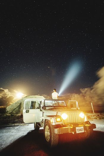 Car on road amidst field against sky at night