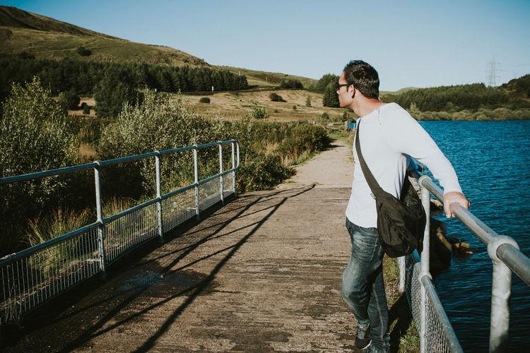 Man standing on bridge over lake against sky