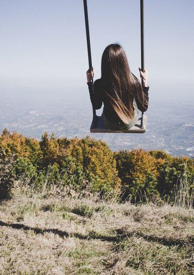 Rear view of woman sitting on swing