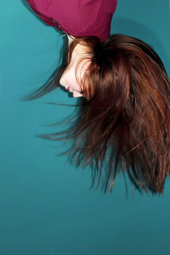 Upside down image of young woman tossing hair against turquoise background