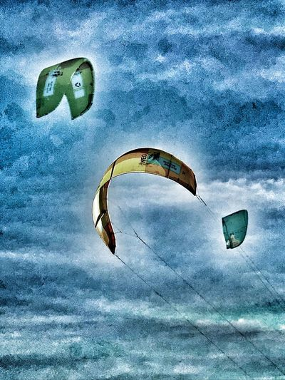 Low angle view of kite flying over sea against sky