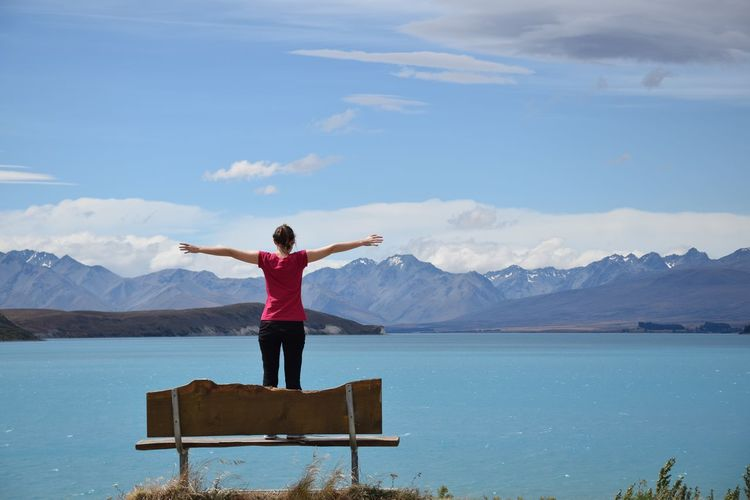 Rear view of woman with arms outstretched standing at lake against mountains