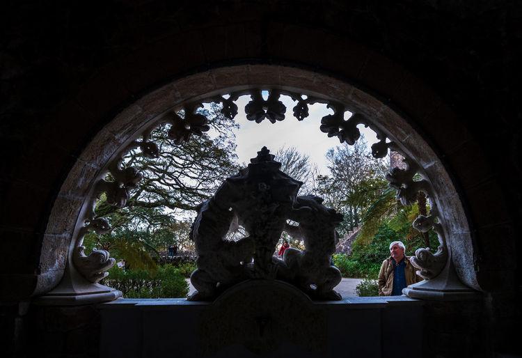 Statue against blue sky seen through arch