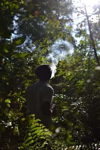 Man exhaling smoke while standing amidst plants