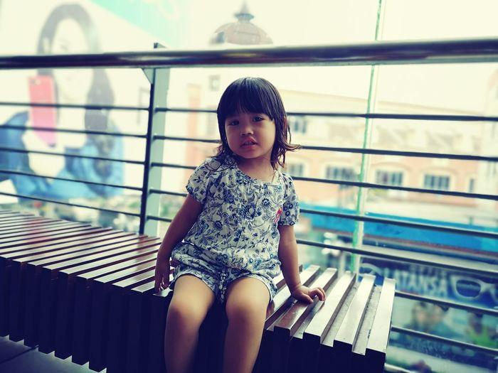 Portrait Of Cute Girl Sitting On Seat