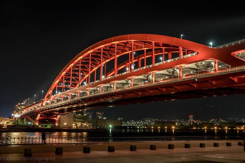 Illuminated Arch Bridge Over River In City Against Clear Sky At Night
