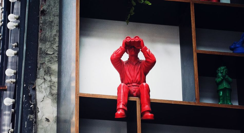 Statue of man looking through binoculars