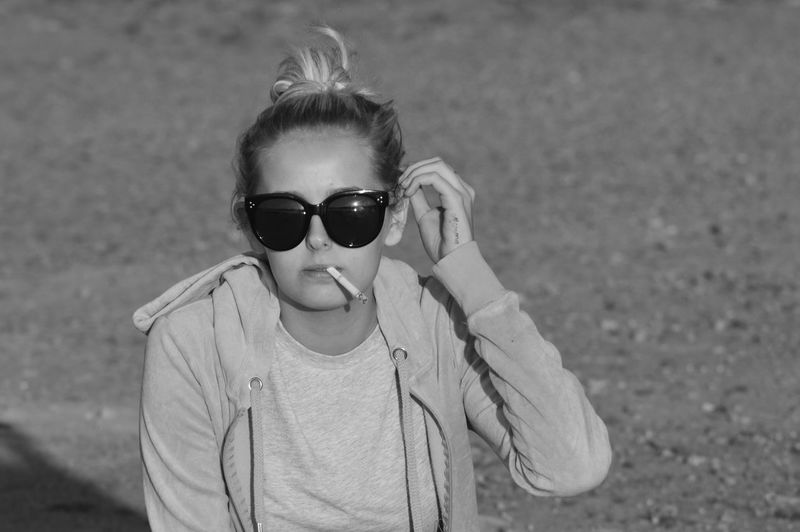 Portrait Of Woman In Sunglasses Smoking Cigarette Outdoors