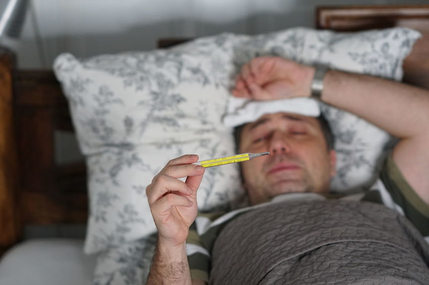 Sick man in bed measuring the temperature and looking at the thermometer Pain Bronchitis Cold And Flu Coughing Disease Fever Headache Health Care Ill Illness Illnesses, 'cauz They're 3 Important Illnes Insomnia Medical Conditions Sick Man Sickness Temperature Temperature Control Temperature Rising Thermometer Tired Vaccinated Vaccination Vaccine Vaccines Virus