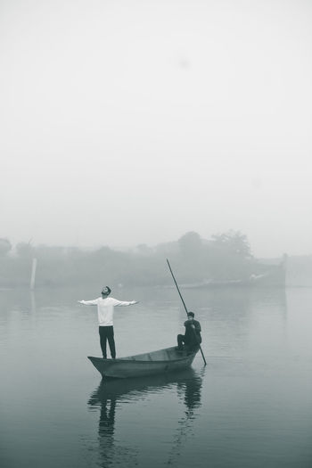 Men in boat on lake against sky during foggy weather