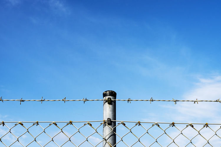 Low angle view of barbed wire against blue sky