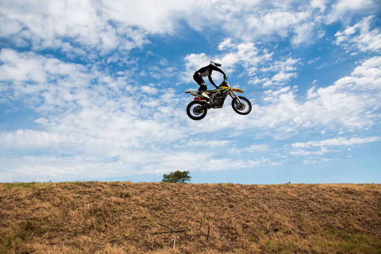 Low angle view of man jumping motorcycle over field against cloudy sky