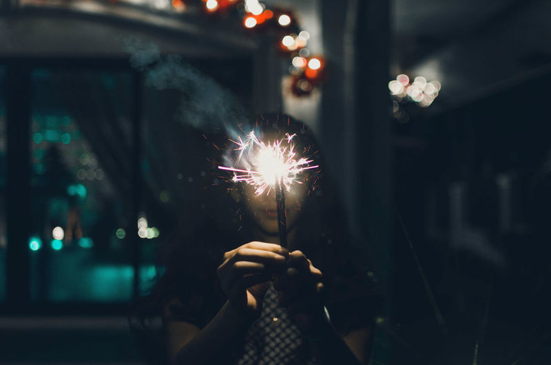 Teenage Girl Holding Sparkler At Night