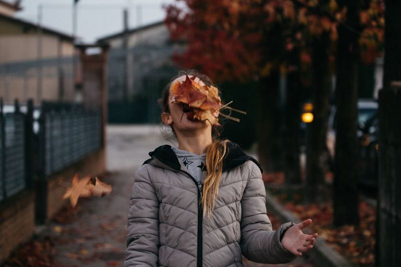 Teenage girl with autumn leaves on face at footpath