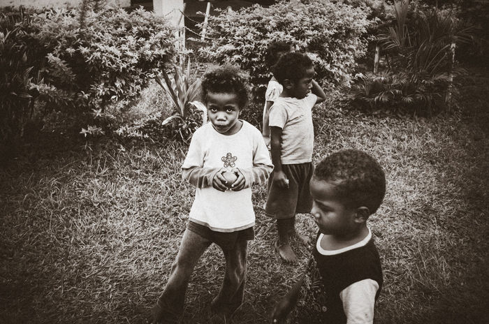 Tangerine Black And White Candid Casual Clothing Child Childhood Children Fiji Grass Kids Looking At Camera Nature Nausori Highlands Outdoors Portrait Real People Standing Street Photography Tangerine Togetherness Village Life The Portraitist - 2017 EyeEm Awards