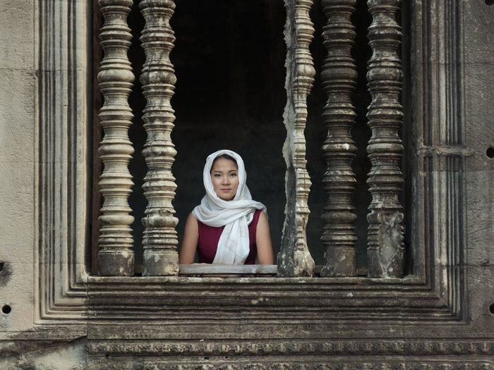 Portrait Of Woman Looking Through Temple Window