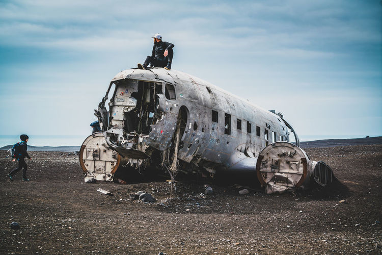 View of abandoned airplane on airport runway against sky