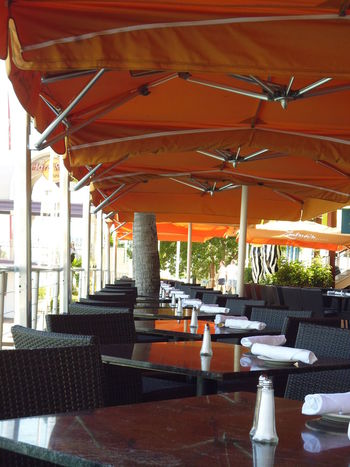 Outdoor Restaurant at Bayside Marketplace - Miami, FL Bayside Marketplace Bayside Miami Mid-Day Meal Month Of January Off-season Susan A. Case Sabir Unretouched Photography Architectural Column Architecture Before Rush Hour Centered Perspective Chair Day Food And Drink Industry Lunch Time Outdoor Photography Outdoor Restaurant Place Setting Ready For Business Restaurant Seat Table Vibrant Color