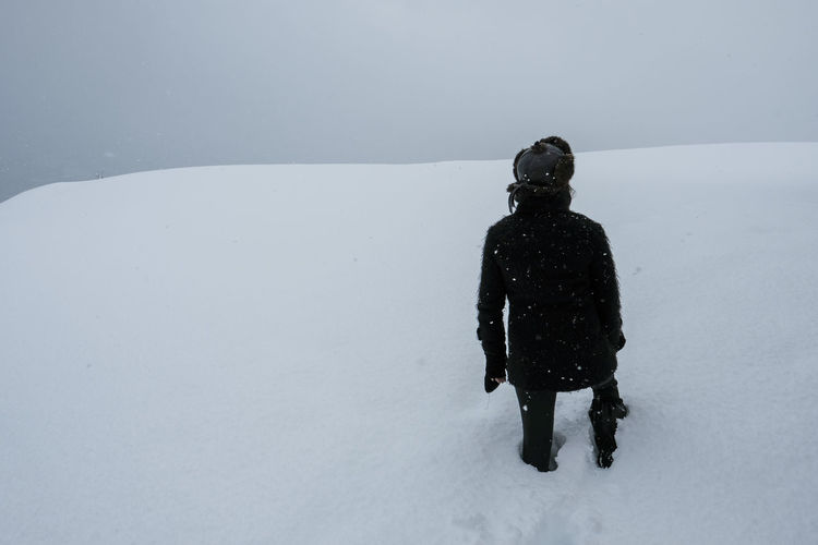 Rear view of person standing on snow field