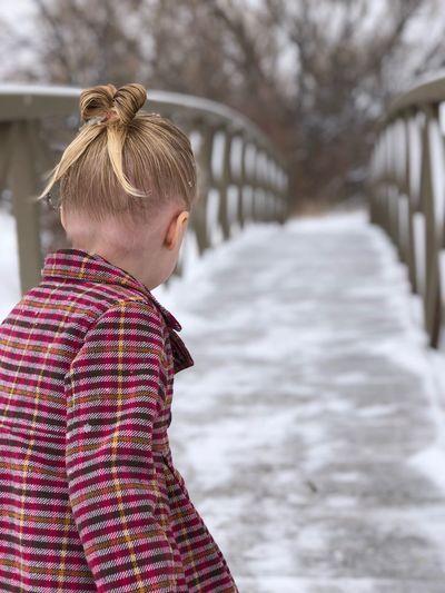 Girl walking on snowy footbridge