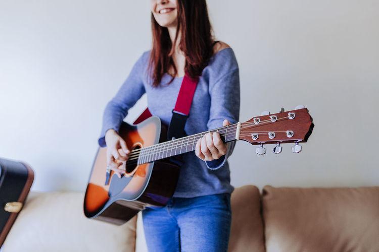 Full length of teenage girl playing guitar