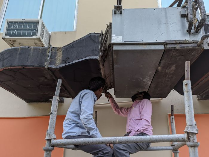 Two workers inspecting outdoor air conditioner ventilation system