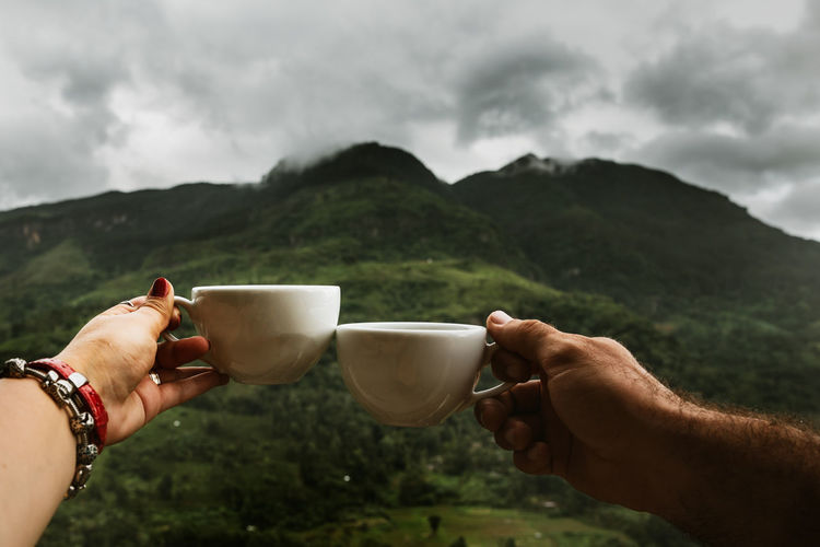 Cropped hands of couple toasting coffee cups against mountain
