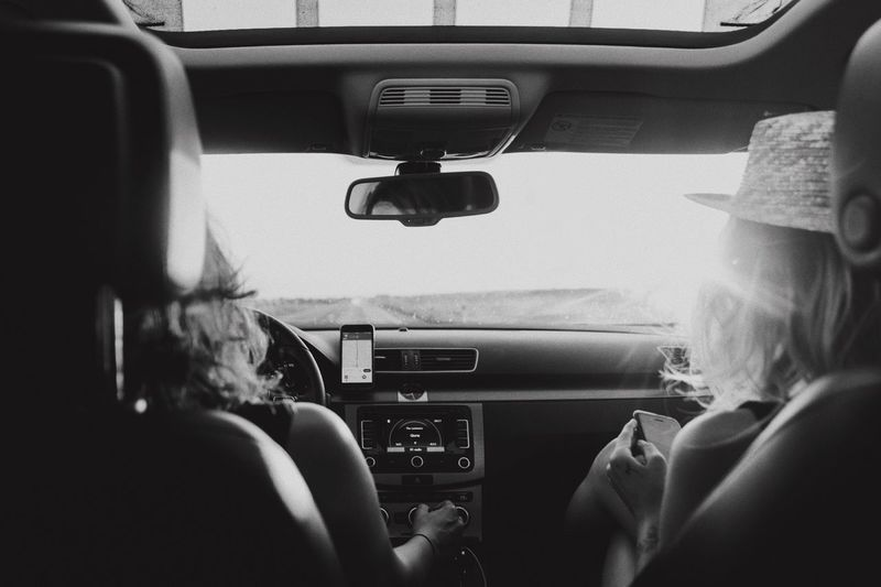 Rear view of women sitting in car