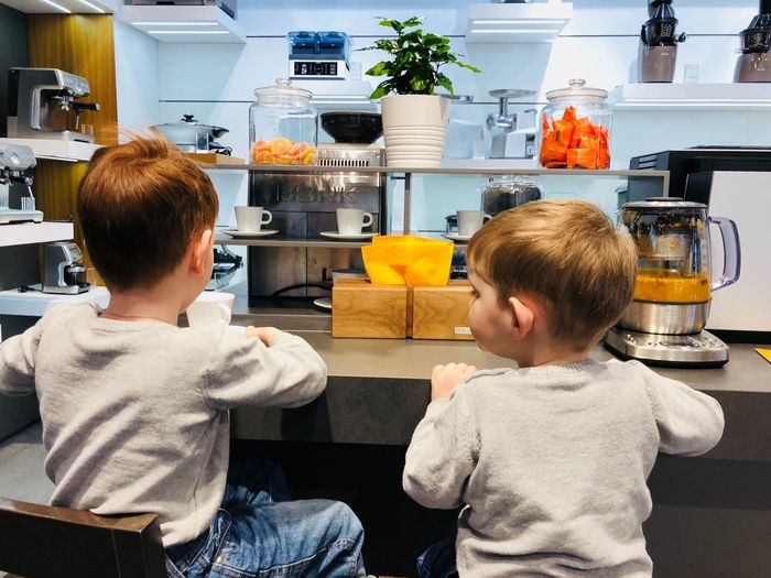 Rear view of boys sitting in kitchen