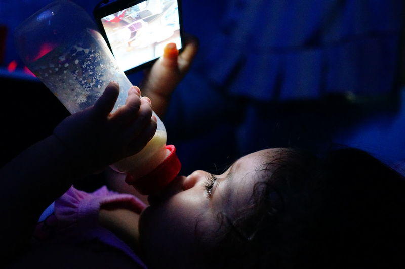 Close-Up Of Girl Using Smart Phone While Drinking Milk