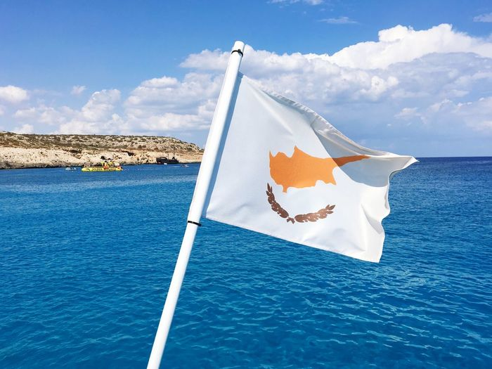 Flag on boat in sea against blue sky
