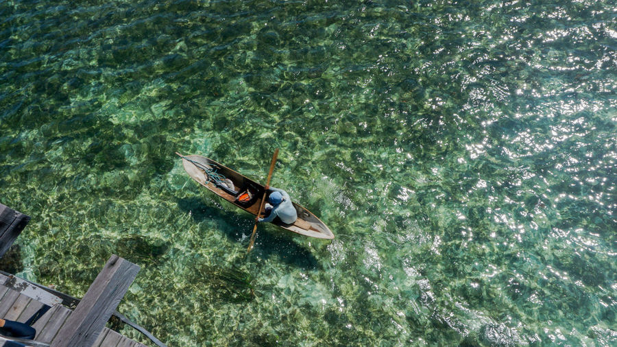 High Angle View Of Man Rowing Boat On Sea