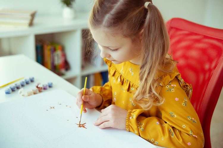 Girl painting on paper at home