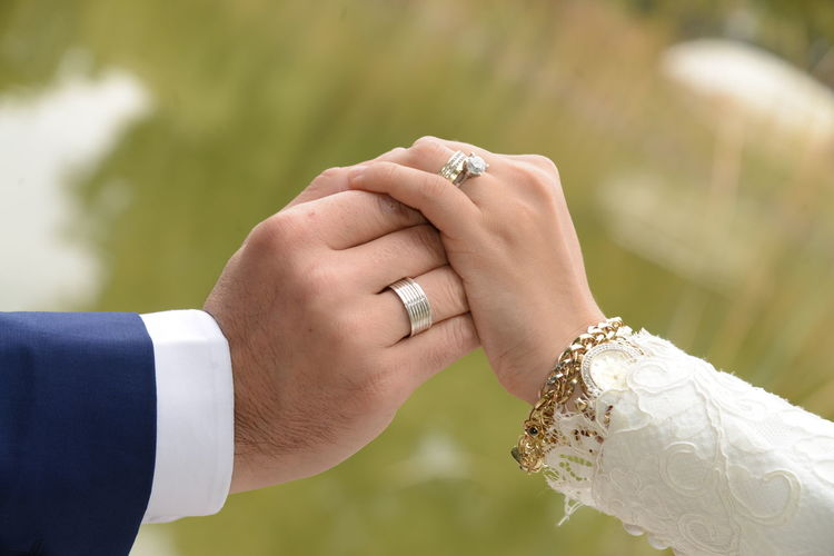 Cropped Image Of Bride And Groom Wearing Rings Against Tree