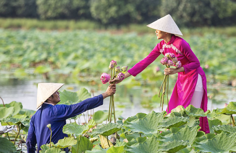 Side view of man giving flowers to woman in lake