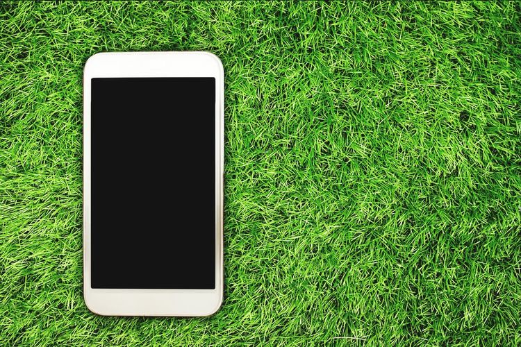 Close-up of smart phone on grass