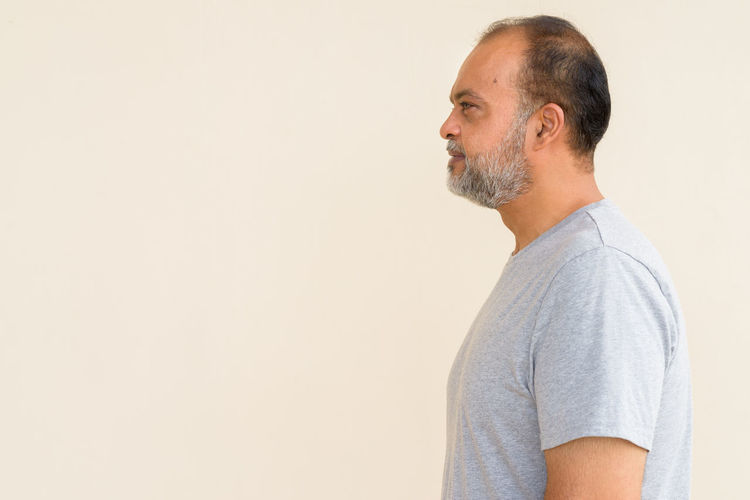 Side view of man looking away against white background