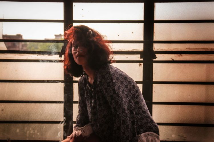 Young woman with tousled hair sitting against old window