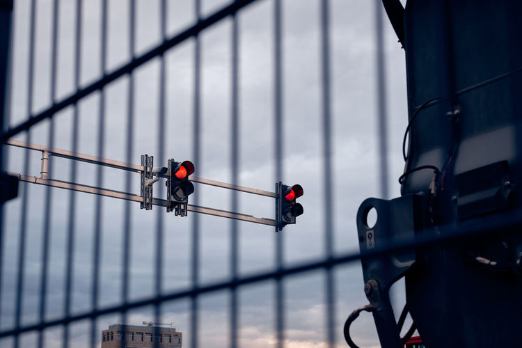 Red traffic lights and cctv camera behind metal fence